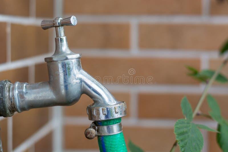 Metal a torneira de água com uma mangueira verde unida fora imagens de stock royalty free