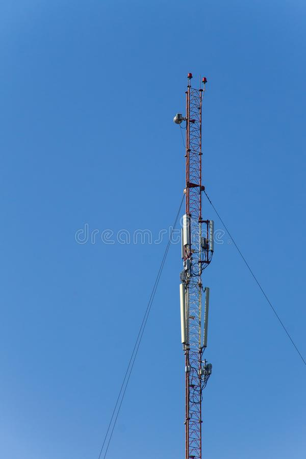 Metal tower with antennas for mobile cell phone communications against blue sky royalty free stock images