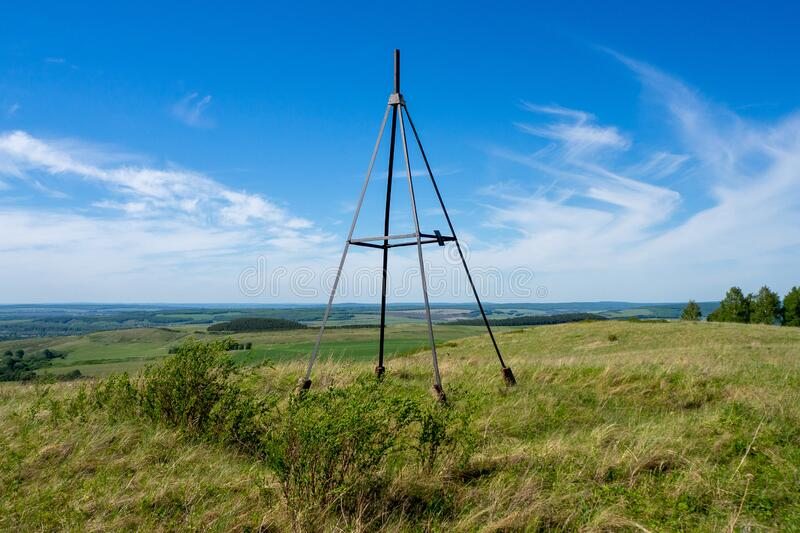 Metal tower on top of a hill. Geodesic, triangulation point. Beautiful summer landscape stock image