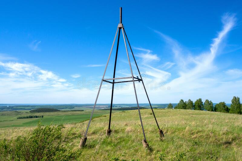 Metal tower on top of a hill. Geodesic, triangulation point. Summer landscape. Metal tower on top of a hill. Geodesic, triangulation point stock photo