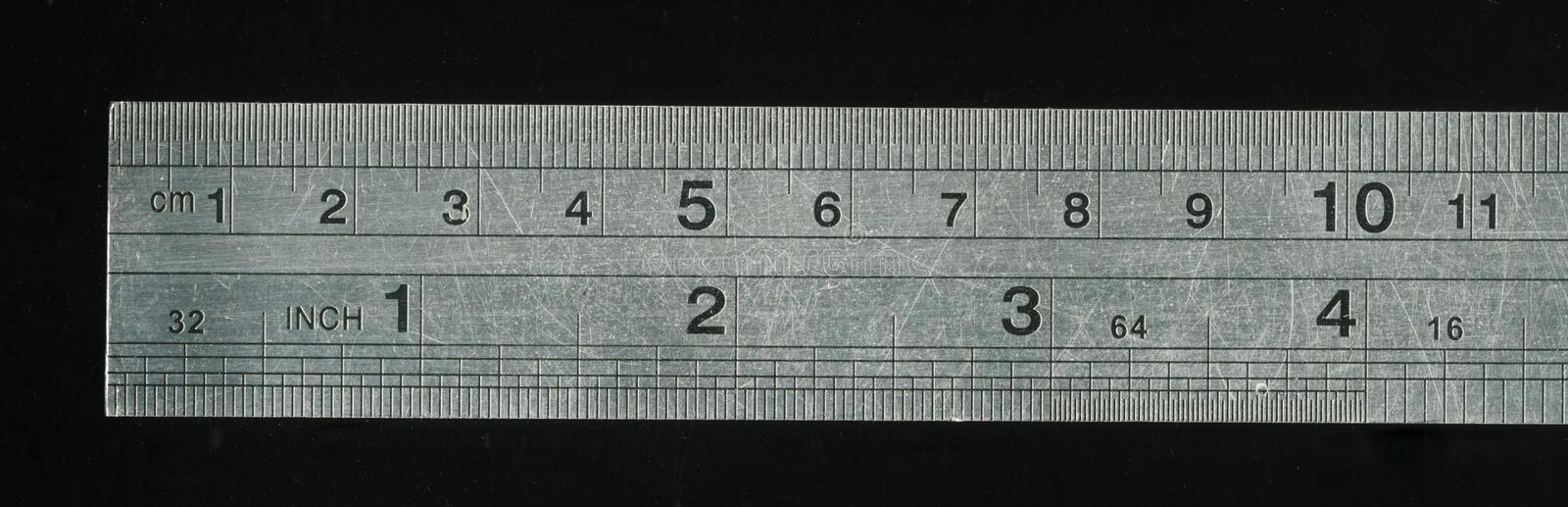 Metal transparent ruler with black background. A fragment old cm - inch ( centimeter - inch ) ruler, isolated on white. 11 cm - 4 inch royalty free stock photography