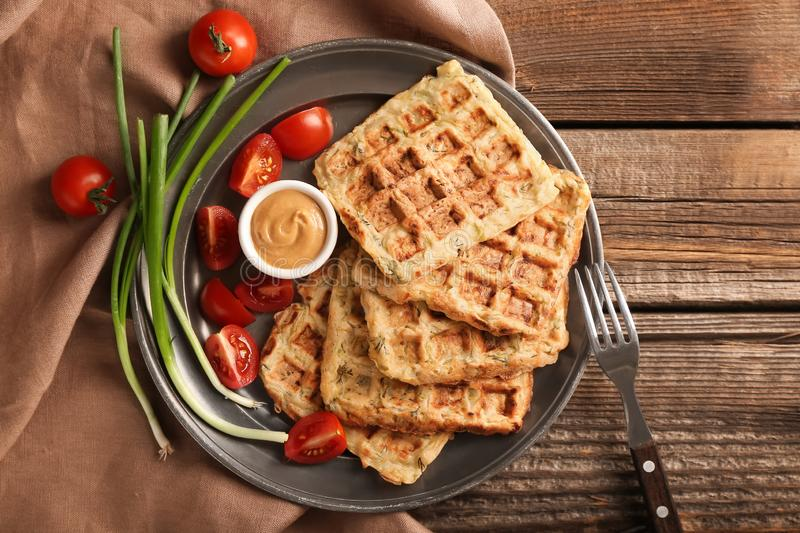 Metal tray with tasty squash waffles and sauce on wooden table royalty free stock photo