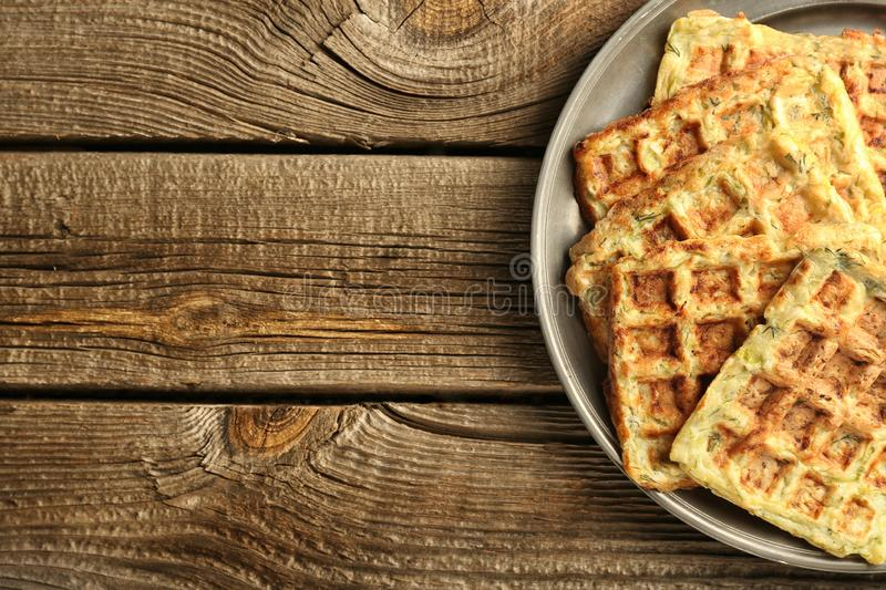 Metal tray with tasty squash waffles on wooden table stock photos