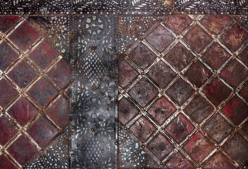 Geometric pattern in form of squares on old rusty metal surface and black painted stripes in top corners and in middle . Metal vintage grunge background stock image