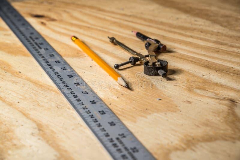Metal władca z kątomierzem i ołówkiem na drewnie wędkował fotografia stock