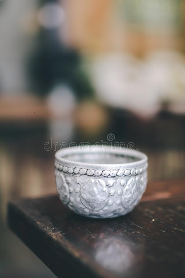 Metal water dipper,metal water bowl for drink. On wooden table in restaurant, Thai stock images