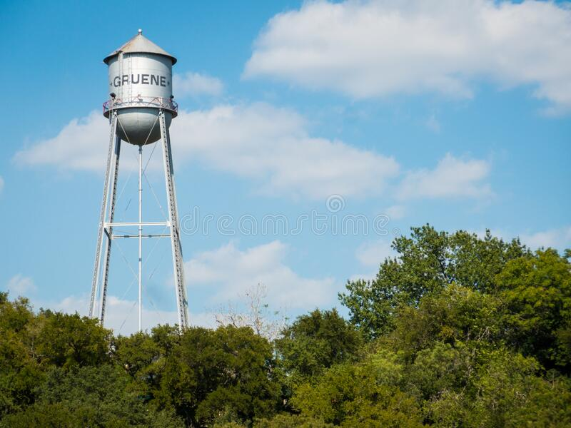 Metal water tank of small texas town Gruene standing high above trees on sunny day. Clouds and blue sky in background. Copyspace available, no people stock images