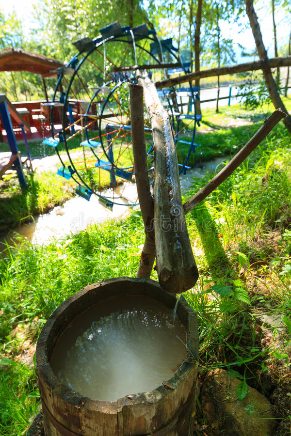 Metal water wheel. Wooden barrel with clean water royalty free stock images
