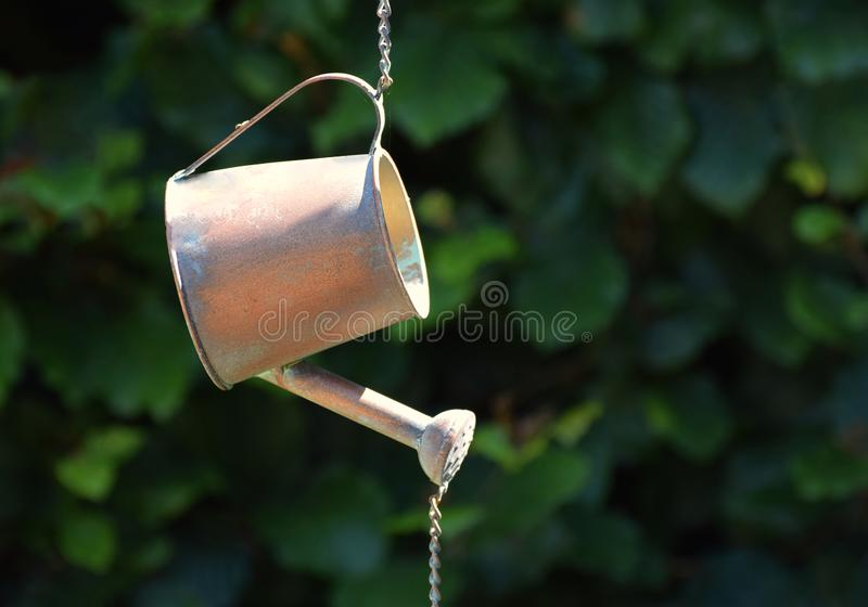 Metal watering can hanging ornament. An ornamental watering can hanging as if pouring out water with copy space against a leafy background stock photos