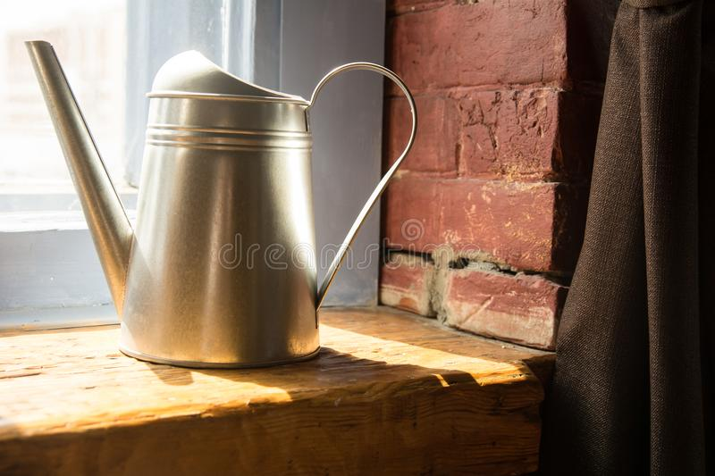 Metal watering can on a wooden window sill royalty free stock image