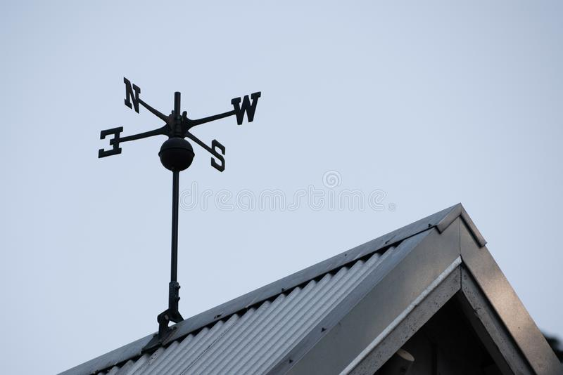 Weather vane on the roof stock image