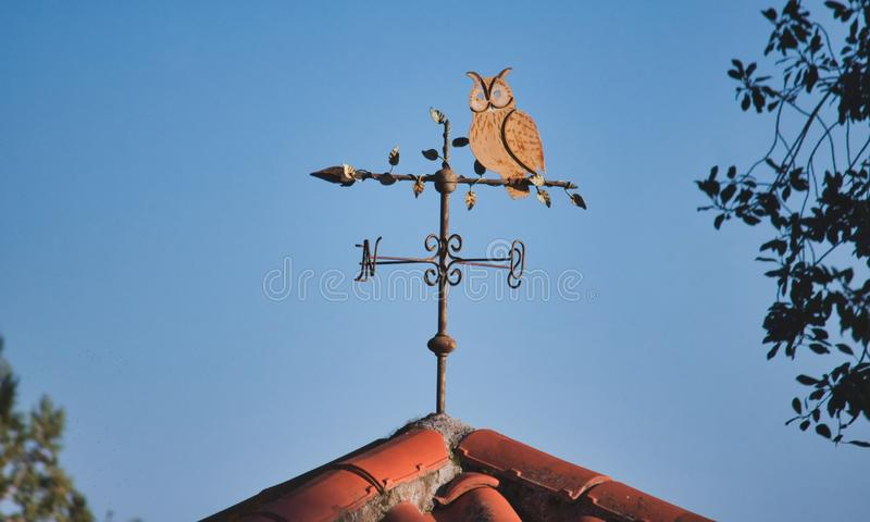 Weather vane shaped like an owl on top of a terracotta tiled roof against a blue sky background royalty free stock photography