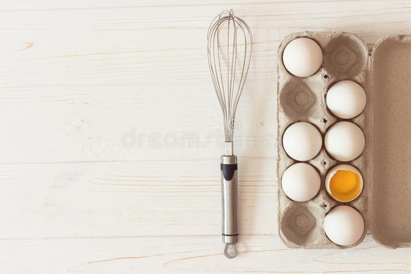Metal whisk and carton of raw white chicken eggs and on white w. Ooden background. Broken egg. Yolk. Top view stock images
