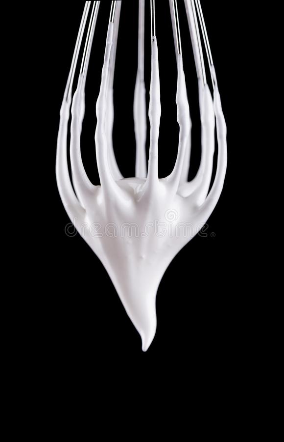 Metal whisk with whipped egg whites, isolated on black background. Clipping path. Metal whisk with whipped egg whites, isolated on black background. Clipping royalty free stock photos