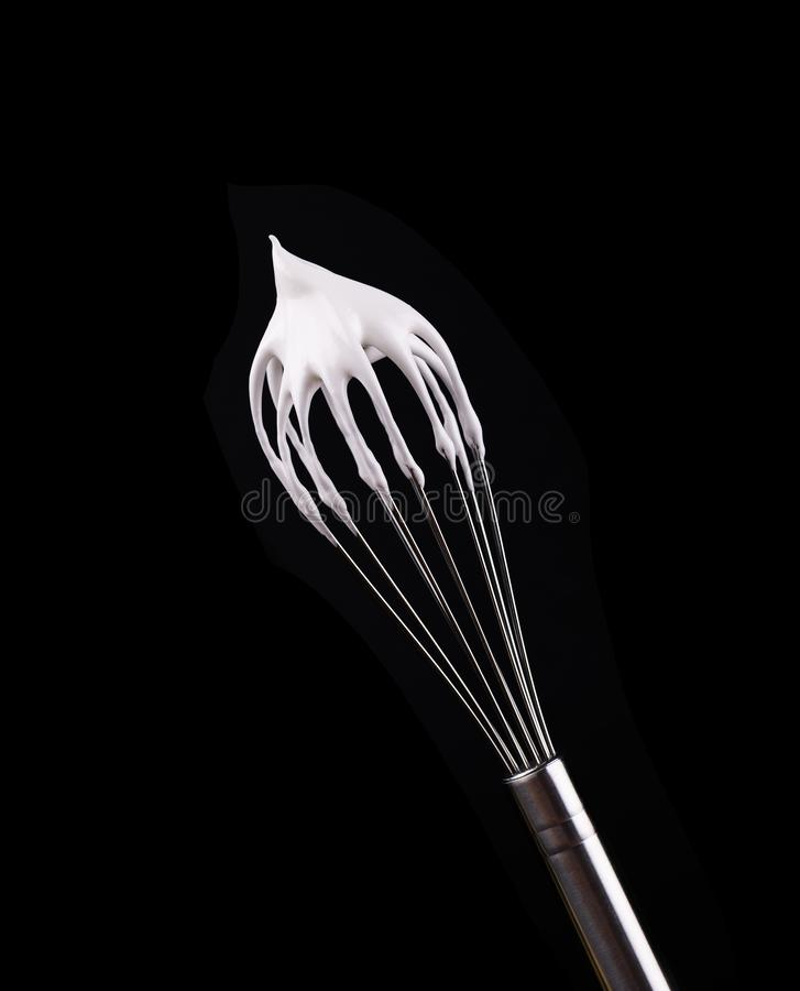 Metal whisk with whipped egg whites, isolated on black background. Clipping path. Metal whisk with whipped egg whites, isolated on black background. Clipping stock photos