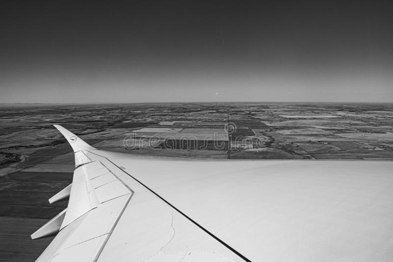 Metal wings two. Photo of the horizon with the wing of a plane in black and white stock photos