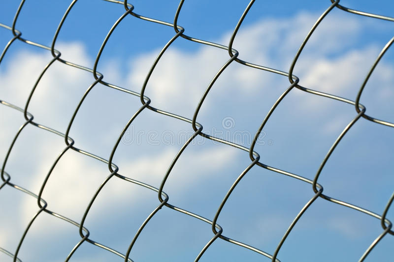 Metal wire fence against sky - slight side view stock photos