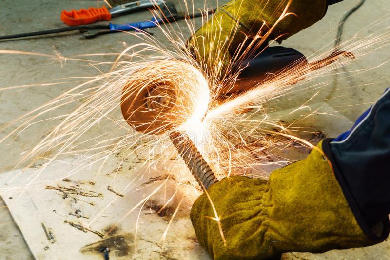 Metal work with a hand-held circular saw. Metalworking with a hand-held circular saw, close up, the disk is blurred in motion, many sparks are visible stock images