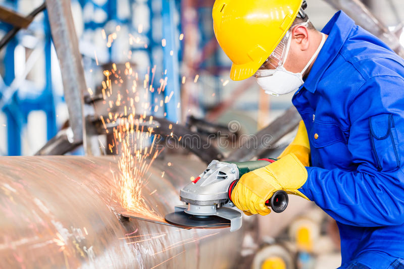 Metal worker in factory grinding metal of pipeline stock image