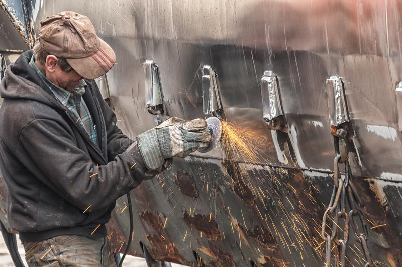 A metal worker is grinding. The wall of a ship with a grinder stock images