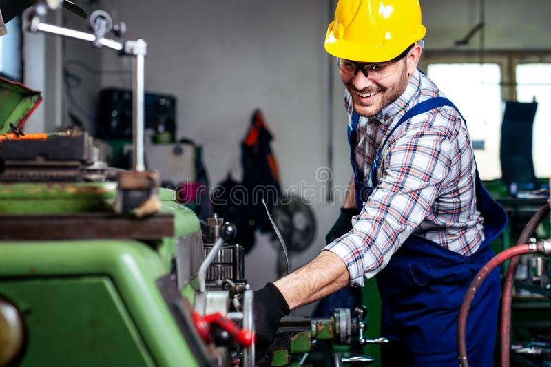 Metal worker turner operating lathe machine at industrial manufacturing factory. stock photography