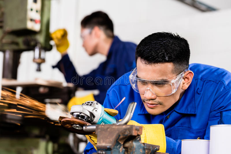 Metal workers in industrial workshop grinding. Two Asian industrial workers in metal factory with electrical grinding tool and power drill machine royalty free stock images
