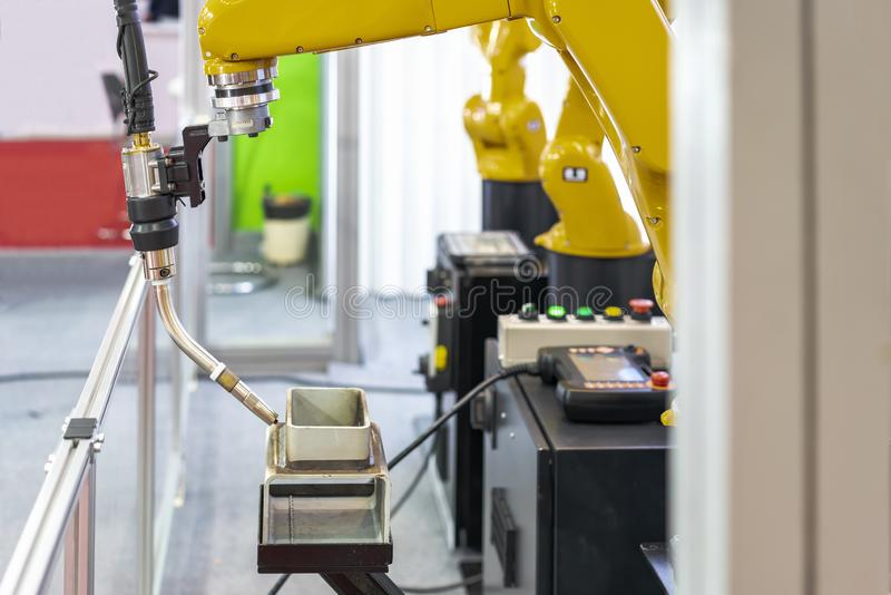 Metal workpieces prepare or setting on table and torch of electric mig with robot arm for automatic welding manufacturing process royalty free stock image