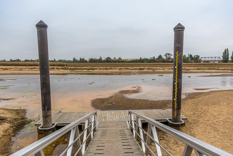 Metal y muelle de madera por el río casi seco, debajo de Pale Sky foto de archivo