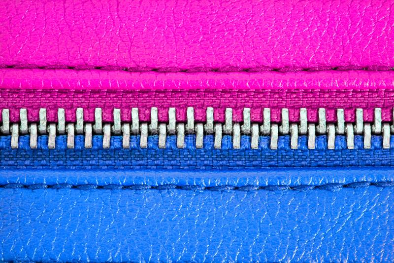 Metal zipper tightly closed binding together two leather layers in pink and blue colours. Concept for male female gender man woman. Metal zipper tightly closed stock images