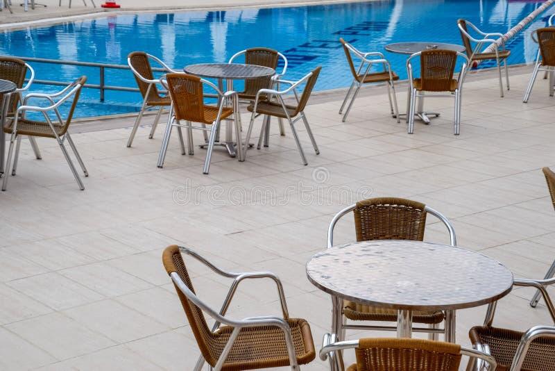 Metali krzesła z łozinowymi siedzeniami wewnątrz i stoły obrazy royalty free