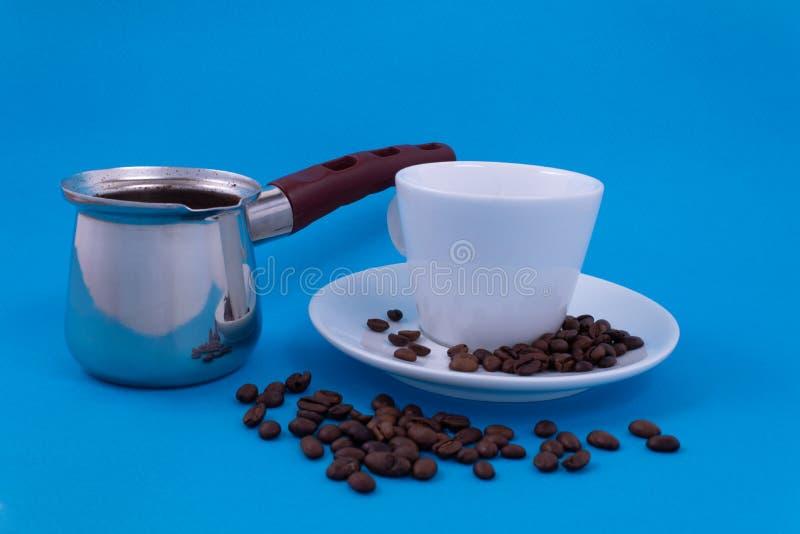 Metali naczynia z warzącą kawą obok białej porcelany filiżanki pozycji na spodeczku fotografia royalty free