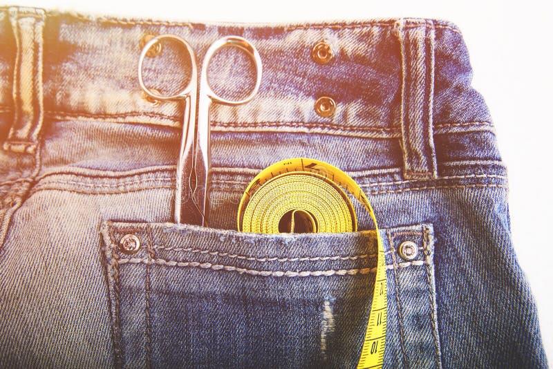 Metali nożyce władca i żółta miara taśmy w drelichów spodniach wkładać do kieszeni obrazy stock