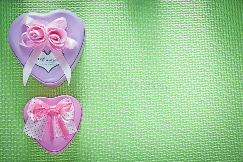 Metali różowi sercowaci teraźniejsi pudełka na zieleni ukazują się wakacje fotografia royalty free