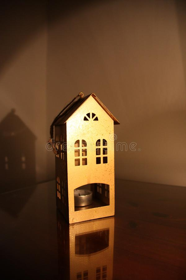 Metalic candlestick in the form of a house on the table in the dark evening with lamp light stock image