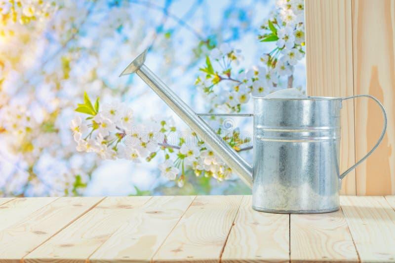 Metaliskt vatten kan läggas på bordet i trädgården fotografering för bildbyråer