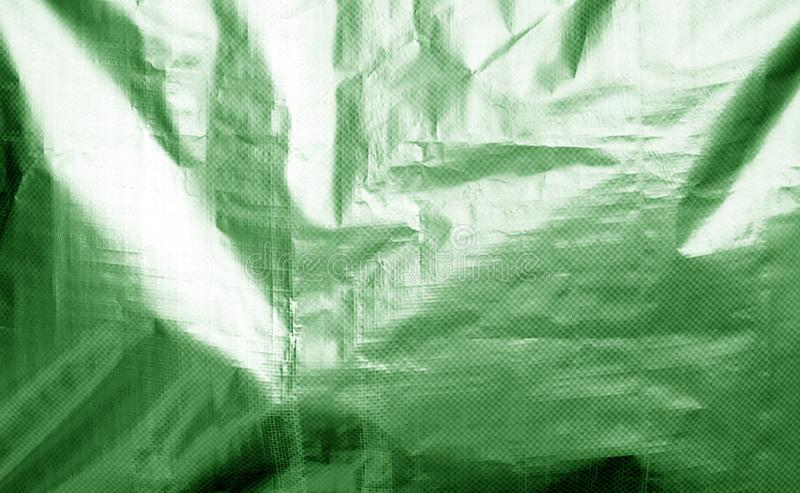 Metalized plastic wrap texture with crumples in green color stock photos