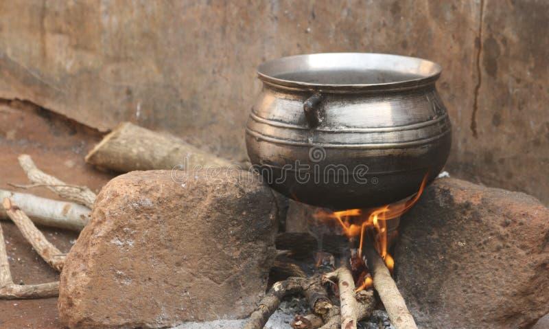 Metall, das großen Kessel über hölzernem Feuer kocht stockbilder