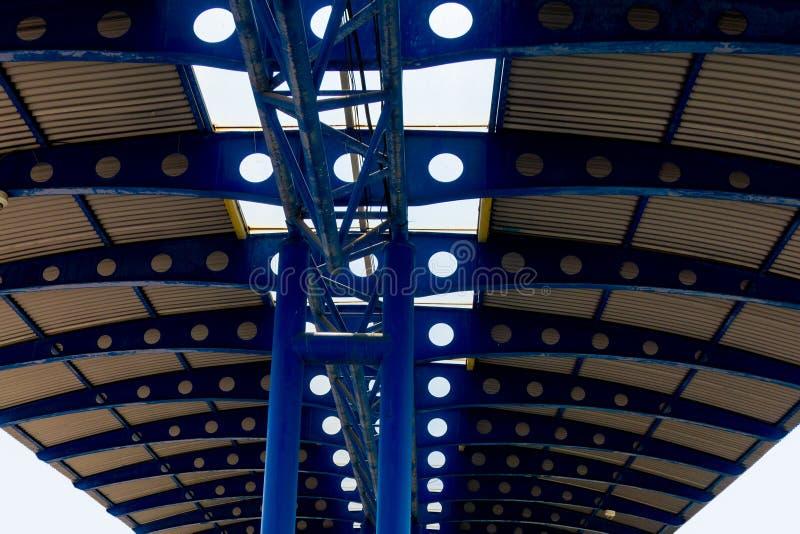 Metall inramad takperspektivsikt Rörkolonner och perforerade servicestrålar i blå färg Genomskinlig central del av taket royaltyfri bild