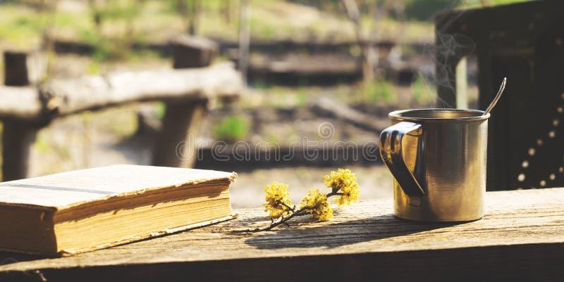 Metall rånar och att blomma filialen och en bok på en trätabell fotografering för bildbyråer