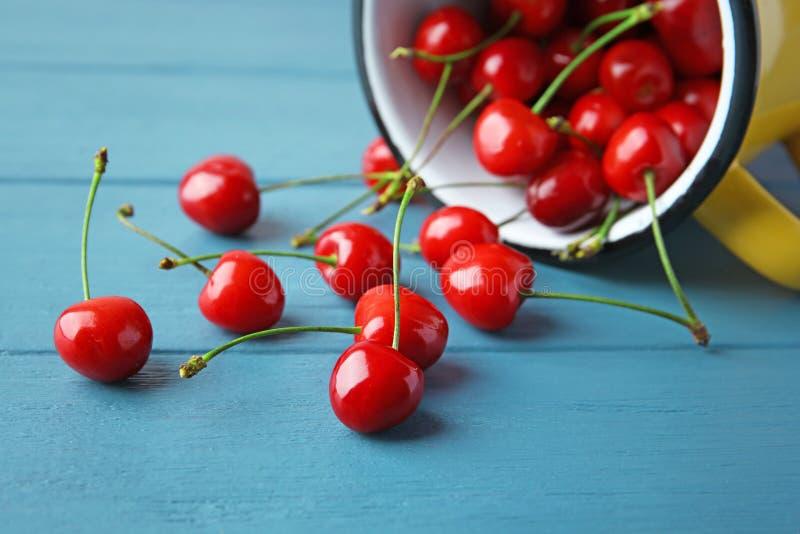 Metall rånar och mogna röda körsbär på trätabellen fotografering för bildbyråer