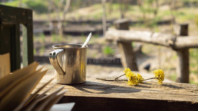 Metall r?nar och att blomma filialen och en bok p? en tr?tabell arkivbild