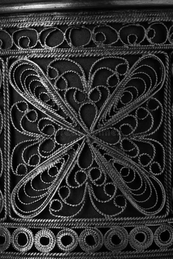 Metall snör åt ingreppet med den blom- modellen Gammal närbild för kopphållare abstrakt bakgrund royaltyfria bilder