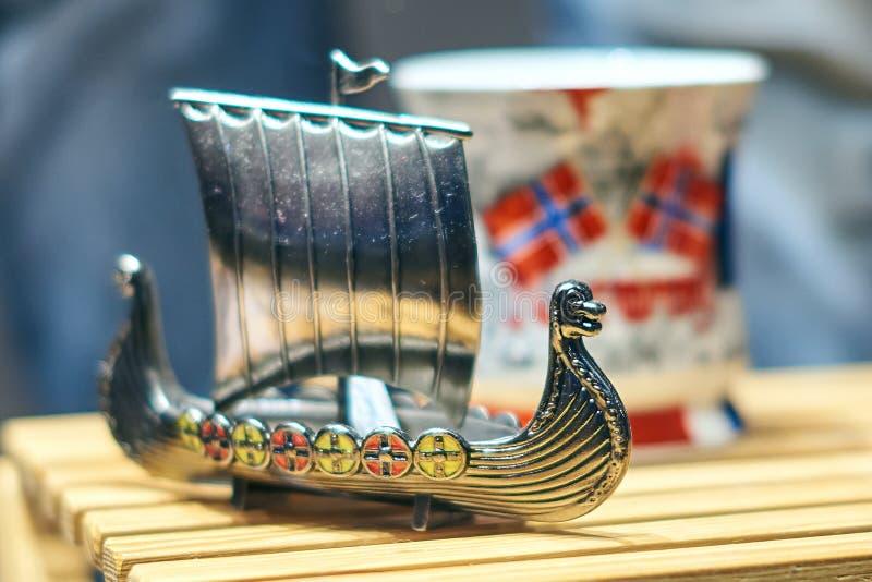 Metall-Viking-Spielzeugschiff alias karve oder knarr und traditioneller norwegischer Becher mit Staatsflagge an der Anzeige stockfotografie