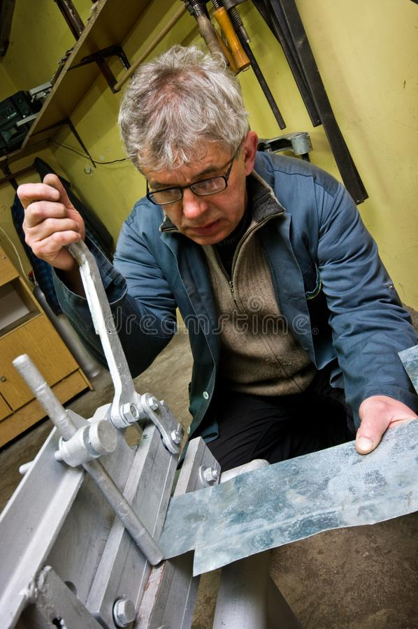 Metallarbeiter- und Guillotinenarbeitskraftmann stockbilder
