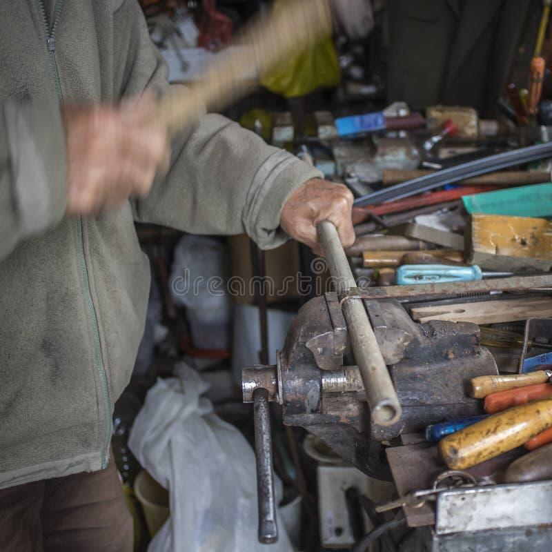 Metallarbetarearbetsmetall med hammaren arkivfoto
