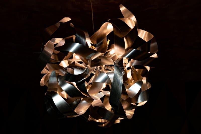 Metallband-Leuchternahaufnahme Moderner Lampenschirm Kupferner und silberner strukturierter Hintergrund Abstraktes chaotisches Mu lizenzfreies stockbild