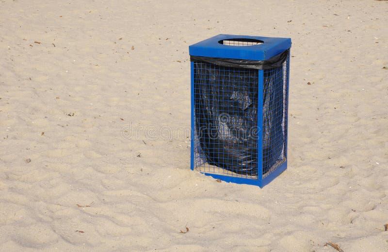 Metallblauer Abfallmülleimer auf Strandsand lizenzfreie stockbilder