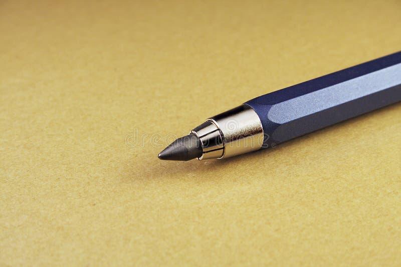 Metallbleistift auf braunem Hintergrund lizenzfreies stockbild