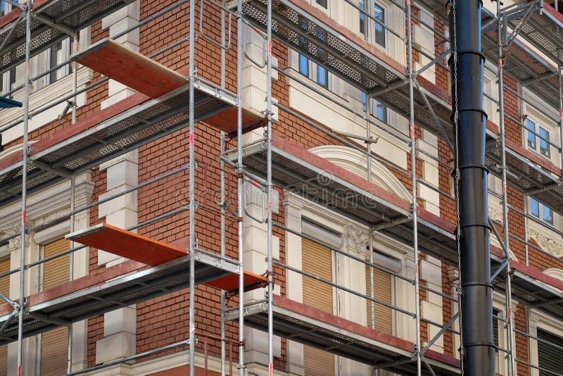 Metallbyggnadsställningar runt gamla byggnader med rött tegel arkivbild