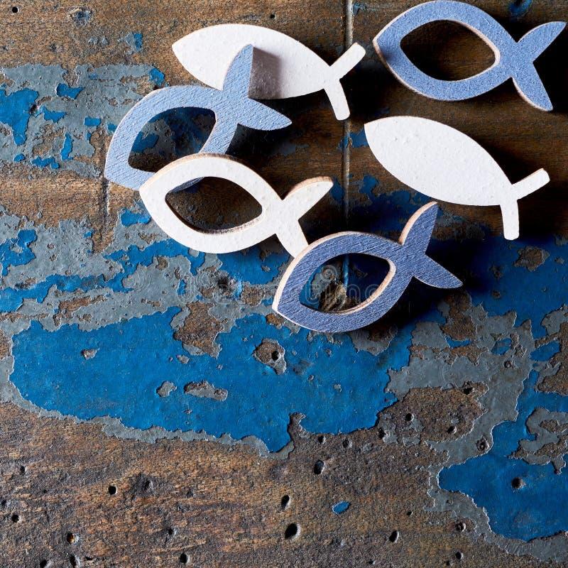 Metallchristliche Fischformen auf hölzernem Hintergrund stockfotografie